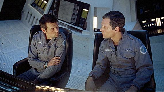 Astronauts Frank and Dave confer while seated in the centrifuge of the Discovery spaceship.